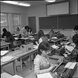 BC Vocational School Commercial Program; students in a classroom typing ; instructor talking to s...