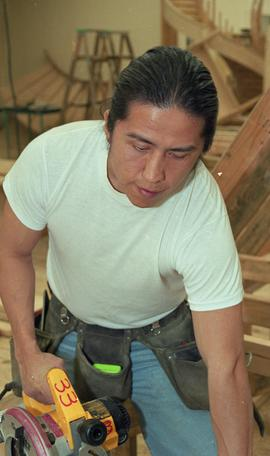 First Nations student wearing a tool belt and using a woodworking tool [1 of 13 photographs]