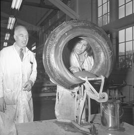 Tire repair, Nanaimo, 1967; instructor talking a student that is repairing the inside of a tire