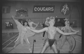 Staff (?) in costumes doing aerobics in a gymnasium [14 of 15 photographs]