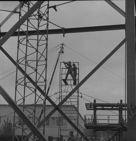 Structural steel, 1971; two workers assembling scaffolding; other steel structures in surrounding...