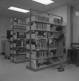 BCIT Burnaby campus library ; a staff member standing next to a shelf reading a book