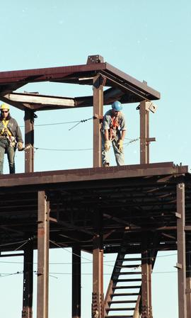 Ironwork, students wearing tool belts, hard hats and uniforms standing at the top of a steel stru...