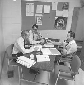 BCVS Graphic arts ; three men at a table talking [1 of 2]