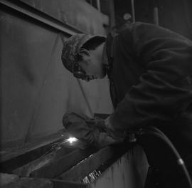 Welding, Nanaimo, 1968; man wearing protective goggles and mitten welding