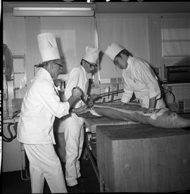 BC Vocational School Cook Training Course ; instructor demonstrating how to butcher meat ; one st...