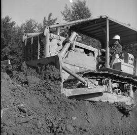 Logging, 1969; a man driving a Caterpillar dozer to move dirt [1 of 2]
