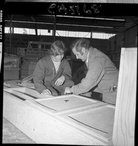 B.C. Vocational School; Carpentry Trades instructor showing a student how to attach hinges to a c...