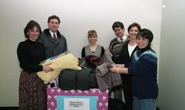 "Staff members with a box labeled ""Warm clothes and blankets for the needy"" [5 of 5 phot..."