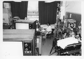 BCIT Broadcast Centre, storage room; woman sitting at a desk smiling for the picture