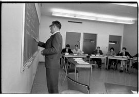 BCIT Business Management image of an instructor writing on a blackboard with students sitting at ...