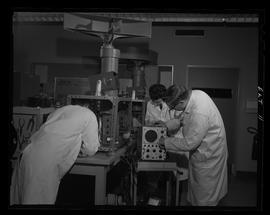 Three men in lab coats working, BCIT Electronics