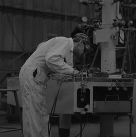 Welding, 1968; man wearing protective goggles welding ; welding equipment in background
