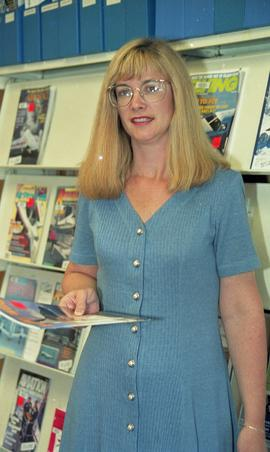 Woman next to magazine rack, Lori Pederson, original Aerospace Technology Campus (ATC) Library [4...