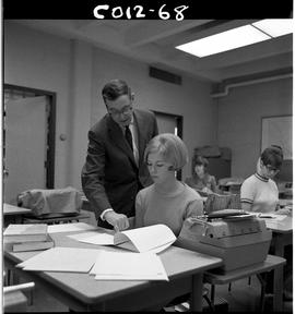 B.C. Vocational School; Commercial Program instructor in a classroom with a student who is sittin...
