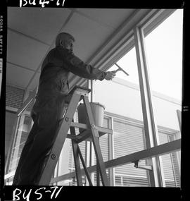 B.C. Vocational School image of a Building Service Worker program student on a ladder cleaning wi...