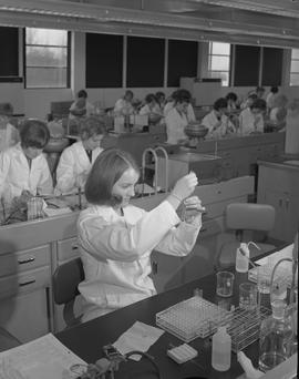 Medical laboratory technology, 1967; a student in lab coat adding liquid to a test tube ; student...
