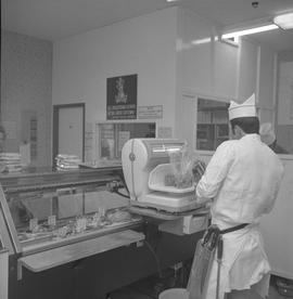 Meat cutting, 1968;  a man measuring packaged meat on a scale ; meat cooler in background