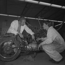 Small engine repair, 1971, Prince George; instructor talking to a student working on a motorcycle...