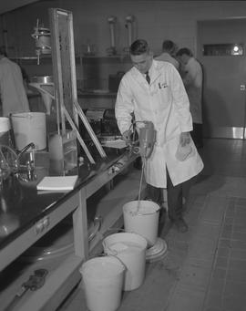 Forest Products, 1966; man in a lab coat using a device to test liquid in a bucket on the floor ;...
