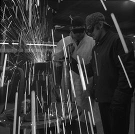 Welding, Terrace, 1968; instructor talking to a student welding; sparks flying everywhere