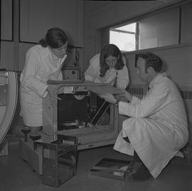 Medical radiography, 1968; three people in lab coats changing film in an x-ray generator [1 of 2]