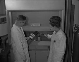 Medical isotope option, Health technology, 1967; two people in lab coats testing radioactive mate...