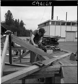 B.C. Vocational School; Carpentry Trades student building roof rafters in the yard outside the Ca...