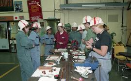 Trades discovery for women; piping, students in helmets and uniforms standing around a table with...