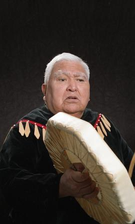 Bob George, First Nations elder, in First Nations garment playing an instrument [10 of 36 photogr...