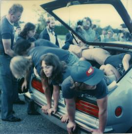Student Rally 1984 ; a group of students laying in or climbing into the trunk of a car [2 of 2]