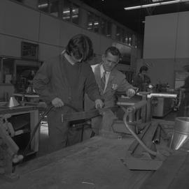 Sheet metal, 1968; instructor observing a student working on a piece of metal in a vice ; student...