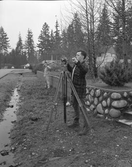 Survey, 1964; two men using surveying equipment in a residential area [1 of 2]