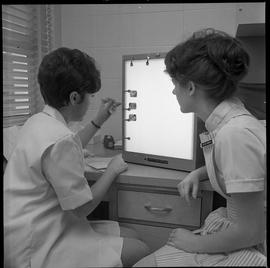 BC Vocational School Dental Assistant program ; two students examining x-rays of teeth [1 of 2]