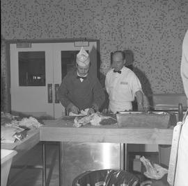 Meat cutting, 1968;  instructor standing next to a student cutting meat
