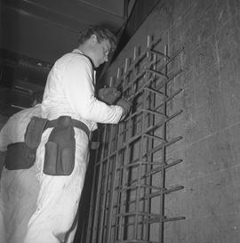 Structural steel, 1971; man cutting wires on a steel grid