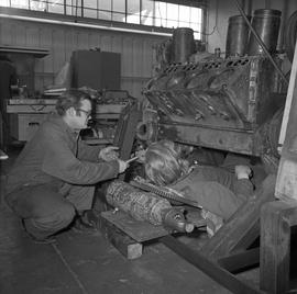 BCVS Heavy duty mechanic program ; man on a creeper working on a motor and another man handing hi...