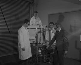 Food Processing Technology, 1966; instructor showing three students in lab coats the controls of ...