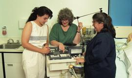 C/Care (students in action), 1993, students with medical machine [3 of 3 photographs]