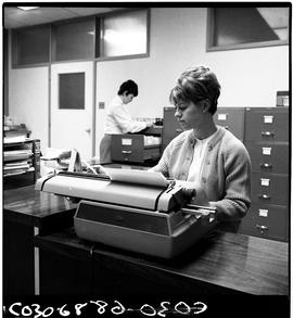 BC Vocational School; a Commercial Program student typing on an electric typewriter with another ...
