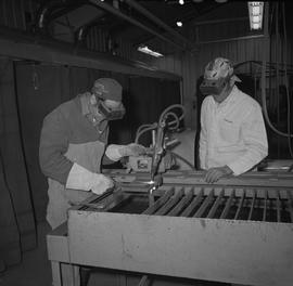 Welding, Terrace, 1968; instructor watching a student use a piece of welding equipment, both men ...