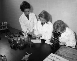 Medical Lab; three women in lab coats sitting at a desk - two women examining test tubes, one wom...