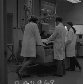 Medical radiography, 1968; four people in lab coats standing around the table of an x-ray generator