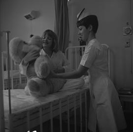 Nursing, 1968; a nurse playing with a child sitting on a bed holding a teddy bear