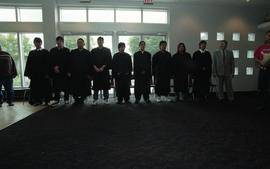 Nine First Nations graduates standing in line beside a staff member (?)