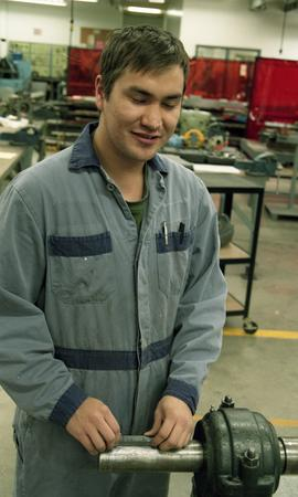 Male First Nations student wearing work overalls handling machinery [4 of 4 photographs]