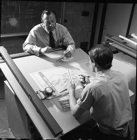 BC Vocational School drafting course ; instructor looking at ruler and talking to a student ; stu...