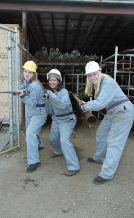 BCIT women in trades; plumbing, students in uniforms and hard hats carrying piping material [4 of...