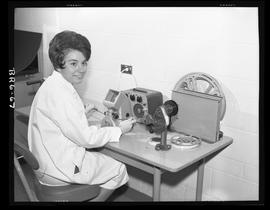 Woman working at Moviscop (viewing reel to reel film)