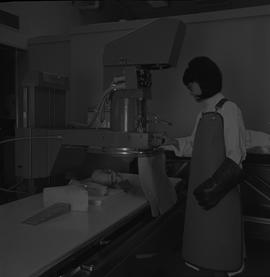 Medical radiography, 1968; woman in radiation protective gear x-raying a skull [2 of 2]